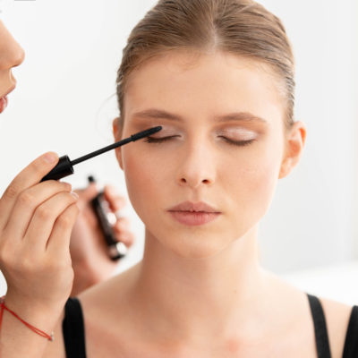 Make up artist applies mascara. make-up master, painting eyes of young beautiful model girl . Make up in process. Beautiful woman face. Front view. Nude
